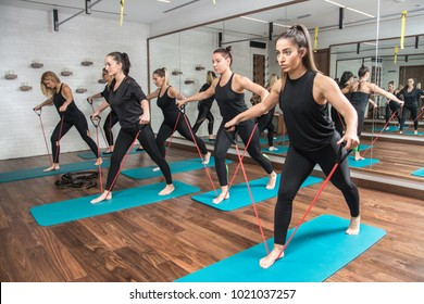Group of sporty girls exercising with a resistance band in fitness studio.