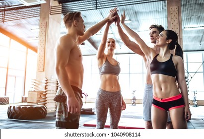 Group of sporty muscular people are working out in gym. Cross fit training. Having rest together and giving five to each other.