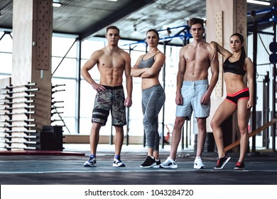 Group of sporty muscular people are working out in gym. Cross fit training. Having rest together, standind and looking at camera