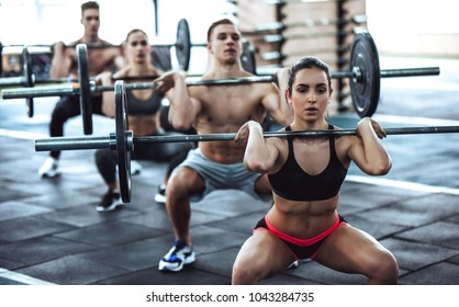 Group of sporty muscular people are working out in gym. Cross fit training. Handsome shirtless men and attractive women are doing exercises with barbells. Weightlifting.
