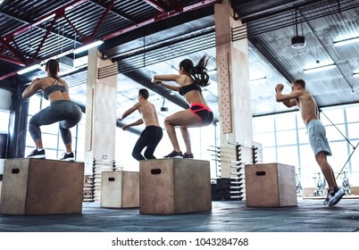 Group of sporty muscular people are working out in gym. Cross fit training. Jumping on a box together.