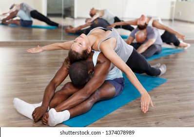 Group of sporty people doing stretching exercises in pairs before a dance training in a modern studio