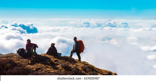 Group of sporty People during Mountain Adventure enjoying top View of Cloud Sky Level