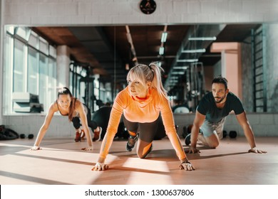 Group of sporty people with healthy habits doing strength exercises on the gym floor. In background mirror.