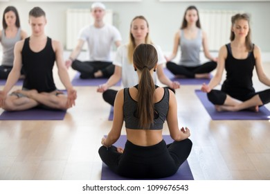 Group of sporty people practicing yoga with instructor, Easy Seat exercise, Sukhasana pose, working out, indoor session full length, students training, studio, teacher rear view. Wellbeing lifestyle
