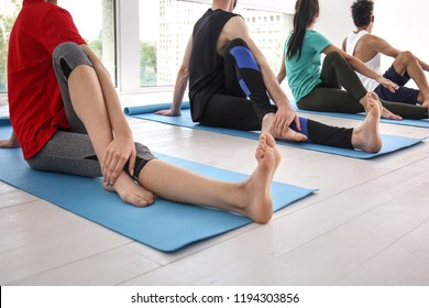 Group of sporty people practicing yoga indoors