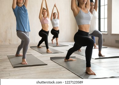 Group of sporty people practicing yoga, doing Warrior one pose, Virabhadrasana 1 exercise, working out, indoor close up, mixed race students training at sport club or yoga studio. Well being concept