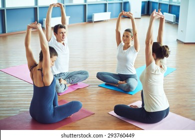 Group of sporty people sitting on mats and doing exercise for relaxation