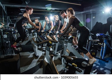 Group of sporty people training on exercise bikes during cycling class in gym.