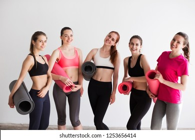 Group sporty woman with yoga mats standing. Female in gym after workout.