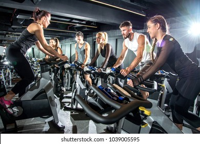 Group of sporty women and men training on exercise bikes together at gym.