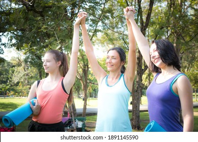 Group sporty women of mother and her daughter standing with mat in yoga sport uniform rejoice raising their hands up after exercise in outdoor class. Team, friendship and helthy lifestyle concept.