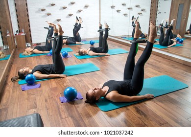 Group of sporty women working out with pilates rings in health club.