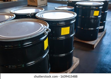 Group of steel drums storing hazardous waste in a sheltered accumulation area