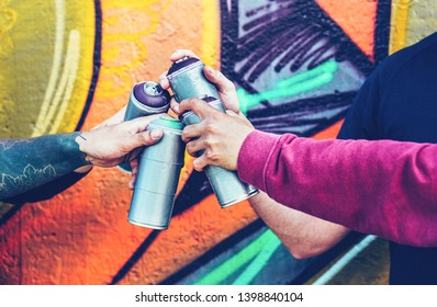 Group of street artists stacking hands while holding spray color cans against colorful background - Concept of young people and modern art graffiti