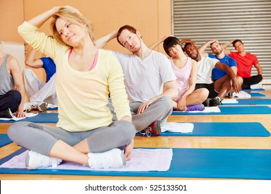 Group stretching in pilates class at the gym