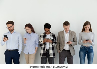 Group of students or businesspeople standing in a row opposite white wall, holding looking on smartphones, waiting for interview. Chatting in social networks online addiction with devices concept