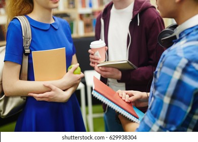 Group of students with copybooks interacting at break