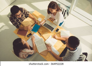 Group of students discussing homework, view from above
