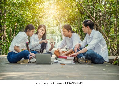 Group of students doing homework and talking  about report together at campus.Education, campus life, friendship and people concept
