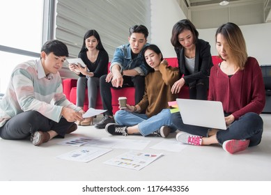 Group of students doing homework together and helping report each other sitting on floor and sofa at apartment