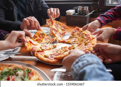 group of students friends eat Italian pizza, hands take slices of pizza in a restaurant, close-up