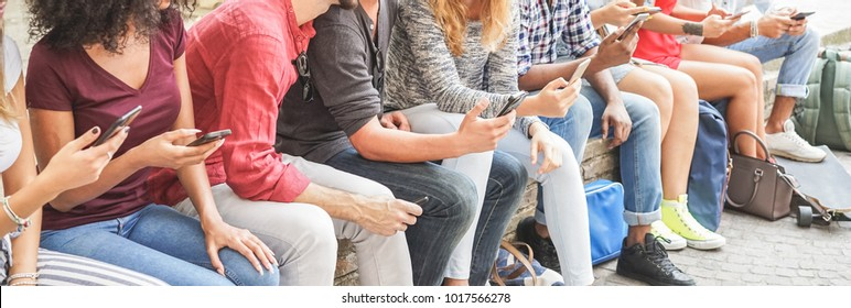 Group of students friends using smartphones  outdoor - Teenager people having fun with technology trends - Youth lifestyle, tech and friendship concept - Focus on man with grey t-shirt mobile phone