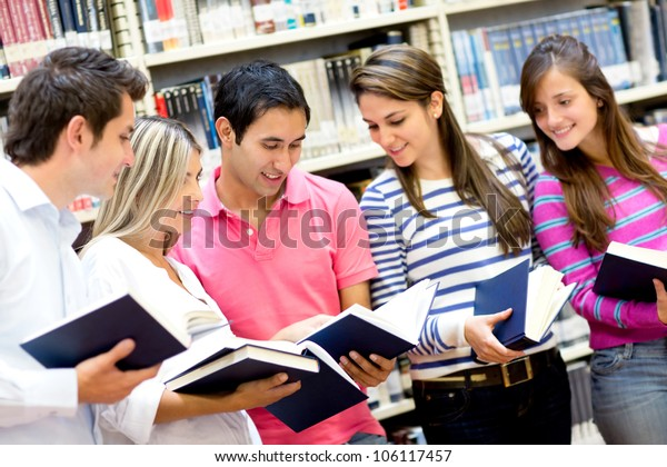 Group of students holding books at the library
