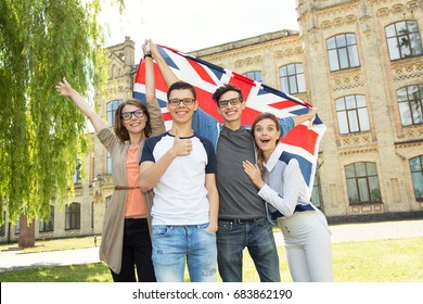 Group of students holding a flag of Great Britain on the university campus background. Friends in United Kingdom.