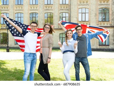 Group of students holding a flag of Great Britain and  a flag of USA standing in the university campus. International language learn course.