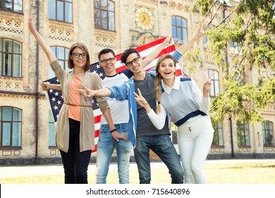 Group of students holding flag of USA on the university campus. Group four happy people having waving American flag. Friends. International language learn course.