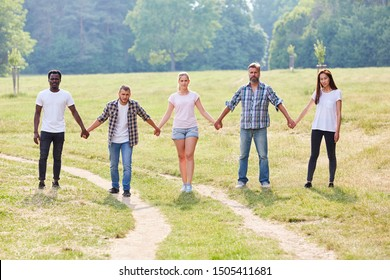Group of students holds hands on the park at the teambuilding event
