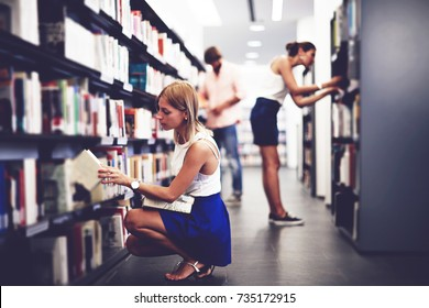 Group of students looking for literature on the book shelves of the university library. Entrance exam preparation