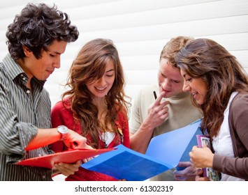 Group of students looking at notebooks and debating