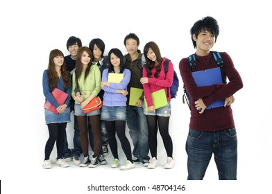 Group Of students with notebooks and paper folders posing--focus on standing young man