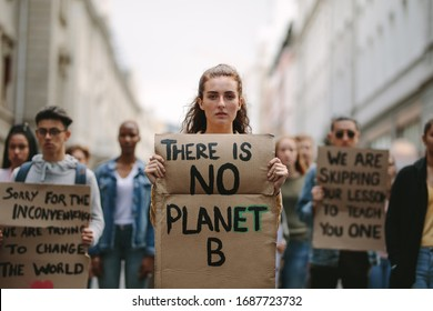 Group of students on the streets demonstrating against climate change. People protesting for problem in ecology, environment, global warming, industrial influence, climate emergency.