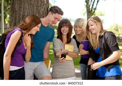 Group of students outdoors looking at a humorous image on a cell phone