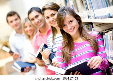 Group of students reading books at the library and smiling