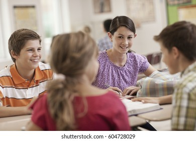 A group of students seated at a desk in a lesson talking to each other,