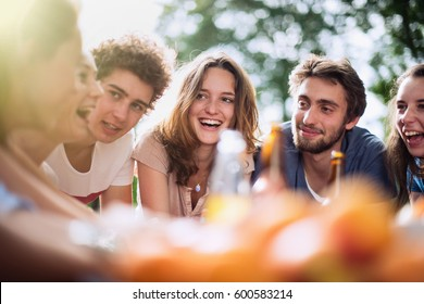 Group of students sitting around a table outside. They enjoy to chat and drink beers. Shot with flare