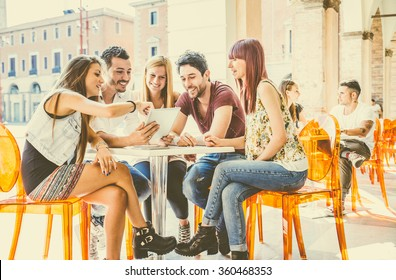 Group of students sitting in a cafe bar looking at tablet - Young cheerful friends having fun with portable computer - Active people watching a funny streaming movie online