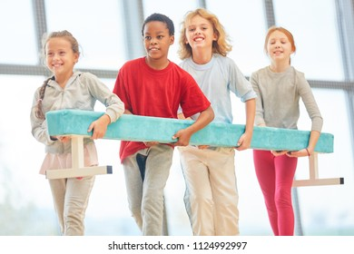 Group of students together carry a balance beam in physical education class