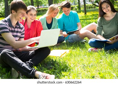 Group of students together preparing for the exam on the grass in the park