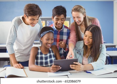 Group of students using digital tablet in classroom at school