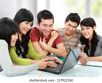 Group of students using laptop together in a classroom