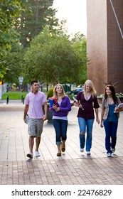Group of students walking, talking, smiling, and carrying books. Vertically framed photo.