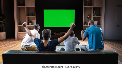 A group of students is watching a TV and celebrating some joyful sports moment, sitting on the couch in the living room. The living room is made in 3D. TV is green screen for further editing.