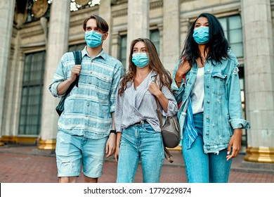 A group of students wearing protective medical masks near the campus.