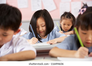 Group Of Students Working At Desks In Chinese School Classroom