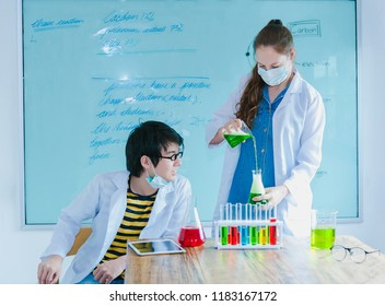 Group of the students working at the laboratory classroom for research. Concentrate young female scientist holding tube and looking at it while sitting at laboratory. Discovering cure.
